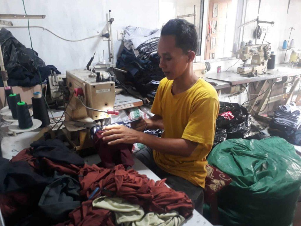 Suami Muslikah Gustiyarmon tengah memasang karet pinggang dengan celana boxer di rumahnya di Kampung Nambo, Desa Kresek, Tangerang.